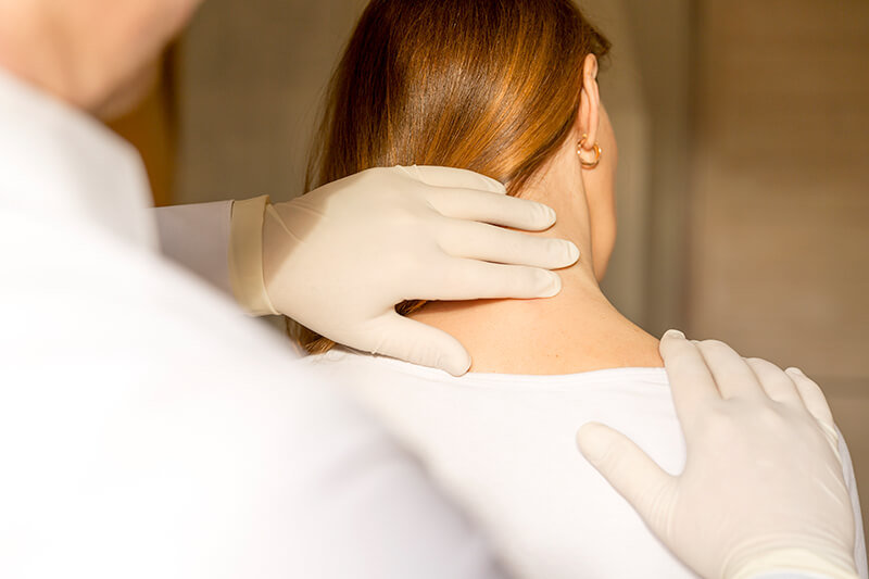 Head and Neck Specialist Surgeon feeling a lump on a female patient's neck