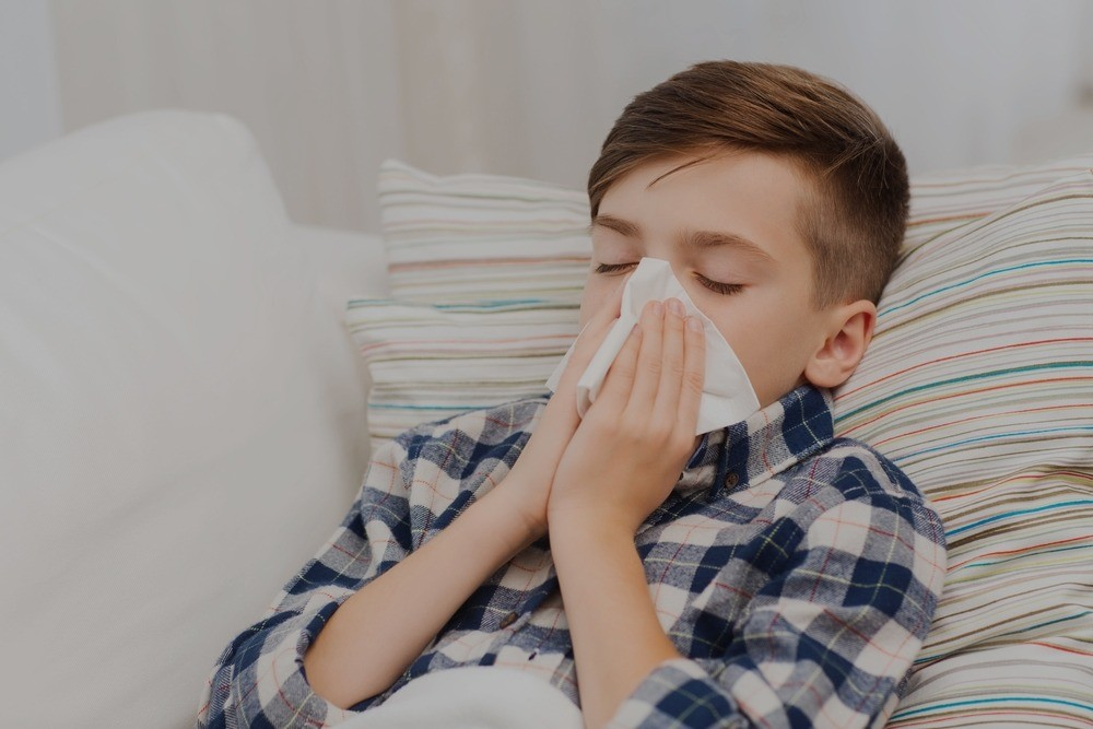 Boy with allergic rhinitis blowing his nose