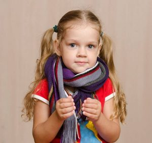 Young girl covers lumps on her neck with a scarf