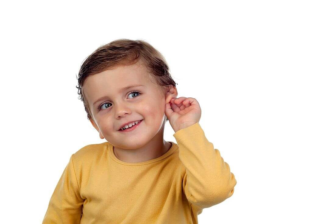Smiling child touching ear after hearing